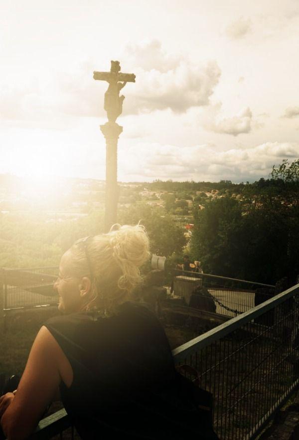 mujer asomada en balcón cercano a Santiago de Compostela junto con un hermoso cruceiro
